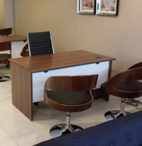 A low cost panel-end style desk in white and walnut giving an expensive look to an estate agents shop
