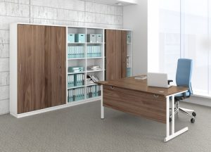 Cantilever type desk with walnut top and modesty panel and white metal framed legs.  Matching storage cupboards and shelving in background with white and walnut wood combinations